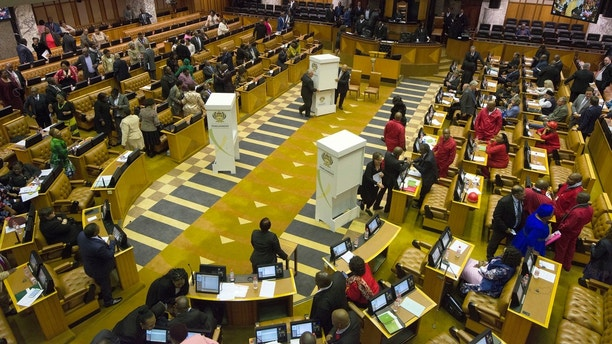 Members of parliament prepare to vote for or against the motion of no confidence against South African president, Jacob Zuma in the South African parliament in Cape Town, South Africa, Tuesday, Aug. 8, 2017. While the president has survived several such votes in the past, this is the first to be conducted by secret ballot. (Rodger Bosch/Pool Photo via AP)