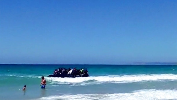 In this image taken from video, a man and young boy watch as a rubber dingy carrying migrants approaches the beach at Cadiz, southern Spain, Wednesday Aug. 9, 2017. Beachgoers watched as around two dozen suspected migrants scattering on the beach. Disembarkations by migrants on Spanish beaches aren't common but have happened before, especially at Spain's north African enclave cities of Melilla and Ceuta, which border Morocco. (Carlos Sanz via AP)