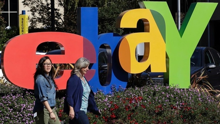 Oct. 17, 2012: In this file photo, two women walk in front of an eBay sign at the company's headquarters in San Jose, Calif.