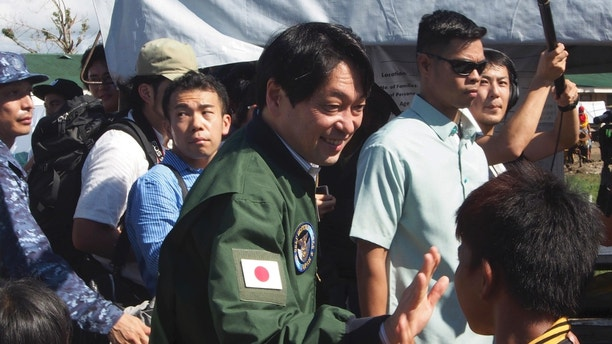 Japanese Defense Minister Itsunori Onodera, left, greets a Filipino evacuee as he visits a school that was used as an evacuation center for typhoon survivors in Tacloban, central Philippines on Sunday, Dec. 8, 2013. Onodera went to typhoon-ravaged Tacloban to look at the magnitude of the disaster for additional Japanese aid. (AP Photo/Oliver Teves)