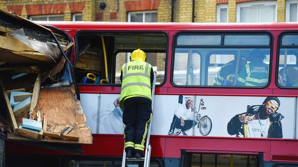 Emergency services personnel examine the inside of a crashed double-decker bus in Lavender Hill, southwest London Thursday Aug. 10, 2017. Transit officials said the bus was heading for the city's Waterloo station when it careened through the plate glass window of a kitchen shop on Thursday morning. (Lauren Hurley/PA via AP)