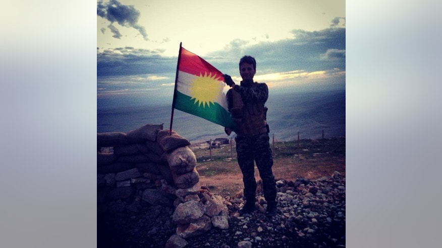 A Kurdish Peshmerga soldier holds the KRG flag on the frontlines of Mosul Dam.