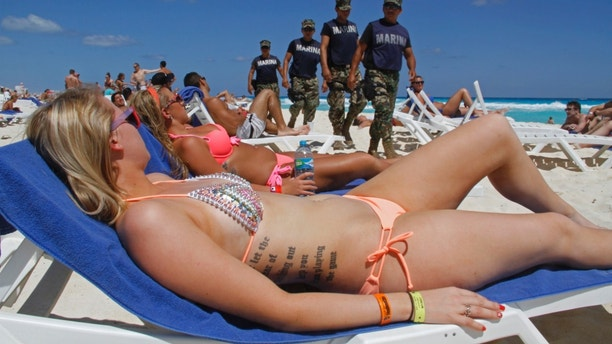 FILE - In this March 15, 2012 file photo, navy sailors patrol as people sun bathe on the beach during spring break in Cancun, Mexico. While American tourism to Mexico slipped a few percentage points last year, the country remains by far the biggest tourist destination for Americans, according to annual survey of bookings by the largest travel agencies. (AP Photo/Israel Leal, File)