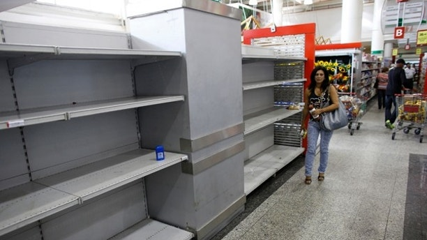 "A woman walks past an empty section where toilet paper should be on display in a super market in Caracas May 17, 2013. Supplies of food and other basic products have been patchy in recent months, with long queues forming at supermarkets and rushes occurring when there is news of a new stock arrival. The situation has spawned jokes among Venezuelans, particularly over the lack of toilet paper. The government announced this week it was importing 50 million rolls to compensate for ""over-demand due to nervous buying"". REUTERS/Jorge Silva (VENEZUELA - Tags: POLITICS BUSINESS SOCIETY) - RTXZQYE"