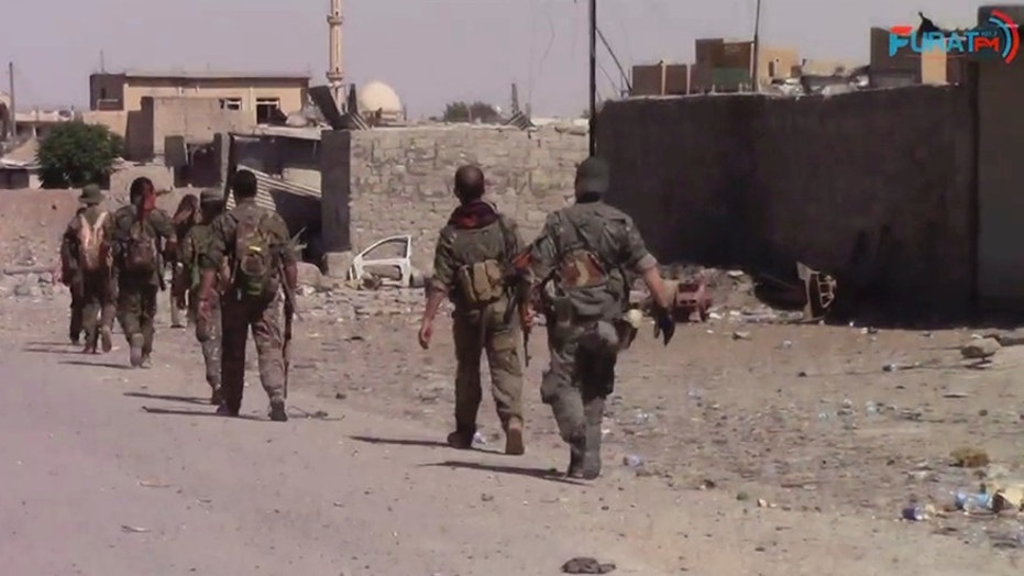 This frame grab from video released Friday, Aug. 11, 2017, and provided by Furat FM, a Syrian Kurdish activist-run media group, shows U.S.-backed Syrian Democratic Forces (SDF) fighters advance in Raqqa, Syria. U.S.-backed Syrian fighters advancing from eastern and western parts of the northern city of Raqqa have linked up for the first time in weeks after launching their offensive against Islamic State group fighters there. (Furat FM, via AP)