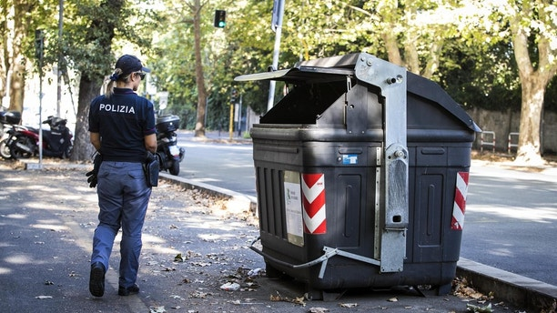 An Italian police officer walks past the site where a trash bin was removed after two amputated legs were found in Rome, Wednesday, Aug. 16, 2017. According to the Italian Police first investigations the part of the human body found belongs to a woman. (Angelo Carconi/ANSA via AP)