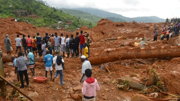 Residents stand as rescue workers search for survivors after a mudslide in the mountain town of Regent, Sierra Leone August 14, 2017. REUTERS/Ernest Henry - RTS1BSZ9