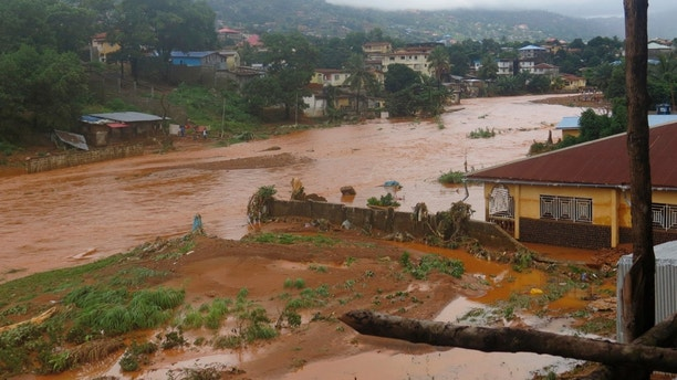 A torrent of water flows through a flooded neighbourhood in Regent, east of Freetown, Sierra Leone Monday, Aug. 14 , 2017. Mudslides and torrential flooding killed many people in and around Sierra Leone's capital early Monday following heavy rains, with many victims still thought to be trapped in homes buried under tons of mud. (AP Photo/ Manika Kamara)