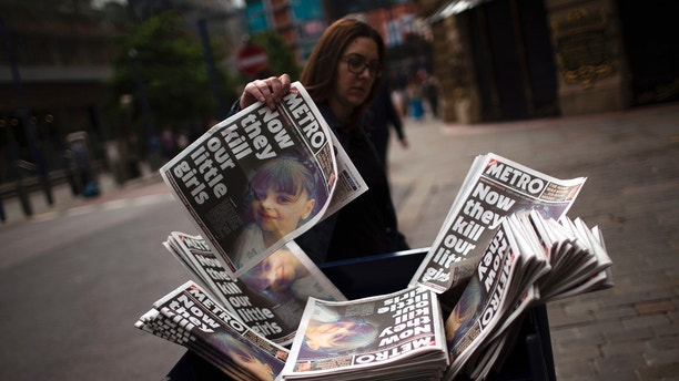 A woman picks a newspaper reporting the news on the suicide attack at a concert by Ariana Grande that killed more than 20 people as it ended Monday night in central Manchester, Britain, Wednesday, May 24, 2017. (AP Photo/Emilio Morenatti)