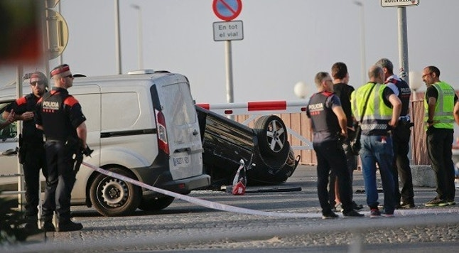 A police officer walks near an overturned car at the spot where terrorists were intercepted by police in Cambrils, Spain, Friday, Aug. 18, 2017. The police force for Spain's Catalonia region says the five suspects shot and killed in the resort town of Cambrils were carrying bomb belts, which have been detonated by the force's bomb squad. (AP Photo/Emilio Morenatti)