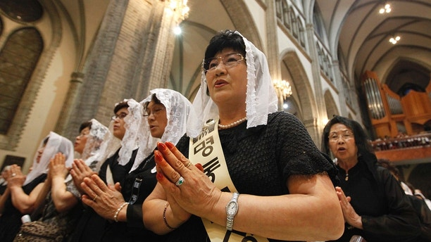 Catholics read a memorial mass as they mourn for the late former President Kim Dae-jung at the Myongdong Cathedral in Seoul