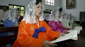 North Koreans read mass at a Catholic church in Pyongyang August 17, 2003. [Civic representatives of North and South Korea have concluded a four-day joint festival in Pyongyang to celebrate the 58th anniversary of the National Liberation Day from Japan's colonial rule (1919-1945) as the Korean Peninsula's security has been an international concern since North Korea disclosed its nuclear weapons programme.] - RTXM5BP