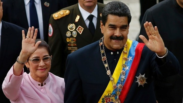 Venezuela's President Nicolas Maduro, right, and his wife Cilia Flores wave as they arrive to the National Assembly building for a session of the Constitutional Assembly in Caracas, Venezuela, Thursday, Aug. 10, 2017. The new constitutional assembly has declared itself as the superior body to all other governmental institutions, including the opposition-controlled congress. (AP Photo/Ariana Cubillos)
