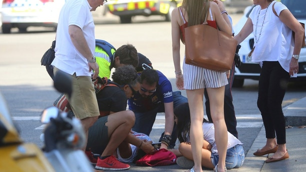An injured person is treated in Barcelona, Spain, Thursday, Aug. 17, 2017 after a white van jumped the sidewalk in the historic Las Ramblas district, crashing into a summer crowd of residents and tourists and injuring several people, police said.