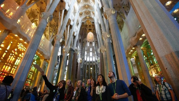 "Visitors of the Sagrada Familia Basilica, designed by architect Antoni Gaudi, in Barcelona, Spain, Wednesday, Oct. 21, 2015.  Barcelona's breathtaking La Sagrada Familia Basilica has begun its final phase of raising six immense tower. Presenting the project Thursday, chief architect Jordi Fauli said the central ""Tower of Jesus Christ,"" the tallest of the six, will rise 172.5 meters (566 feet) high, making it ""the tallest religious building in Europe."" (AP Photo/Manu Fernandez)"
