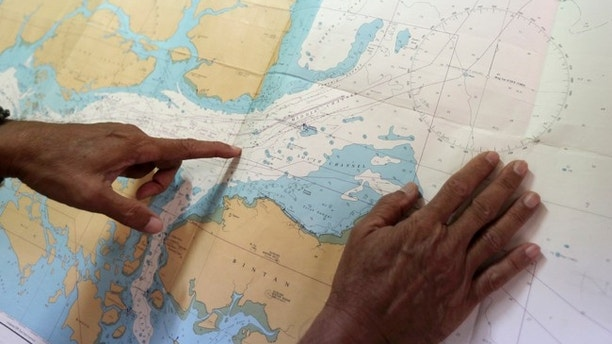 Tan Hua Chiow, a retired Singapore naval officer shows a naval chart and explains to The Associated Press the flow of traffic at sea around the Strait of Singapore on Tuesday, Aug. 22, 2017, in Singapore. Countless ships have made the voyage through one of the world's busiest shipping lane without incident despite its host of navigational challenges, but Monday's pre-dawn collision between a U.S. Navy destroyer and an oil and chemical tanker underlines the risks that normally go unnoticed. (AP Photo/Wong Maye-E)