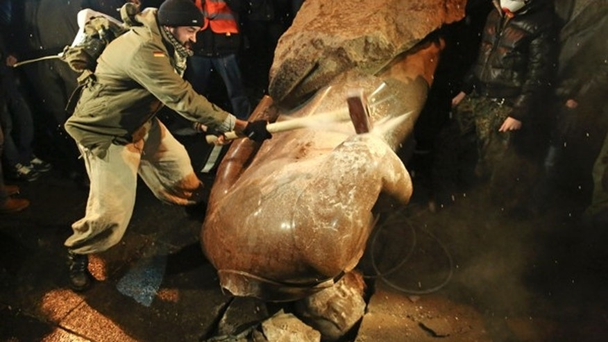 A man holds a sledgehammer as he smashes a statue of Soviet state founder Vladimir Lenin in Kiev.