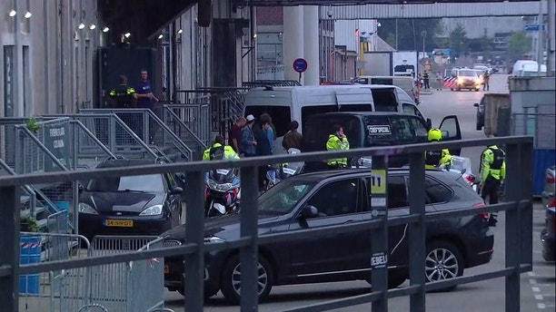In this image taken from video people and security stand around a van in Rotterdam, Wednesday Aug. 23, 2017, after a concert by an American rock band was cancelled Wednesday night following a threat, the city's mayor said. Police detained the driver of a van with Spanish license plates carrying a number of gas tanks inside. (RTL via AP)