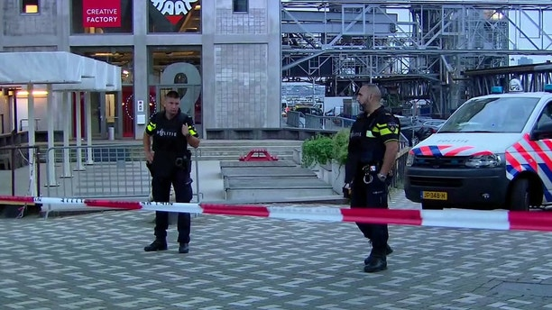In this image taken from video officers stand behind a cordoned-off area in Rotterdam, Wednesday Aug. 23, 2017, after a concert by an American rock band was cancelled Wednesday night following a threat, the city's mayor said. Police detained the driver of a van with Spanish license plates carrying a number of gas tanks inside. (RTL via AP)