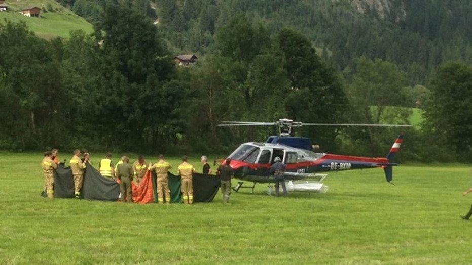 Rescue workers stand next to a police helicopter in Krimmi in the Austrian province of Salzburg.