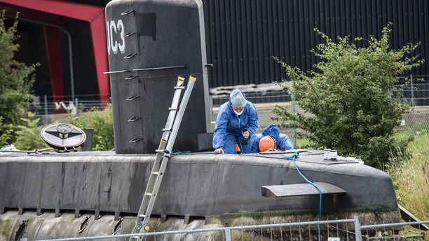 FILE - This is a  Monday Aug. 14, 2017  file photo of police technicians on board the home-made submarine UC3 Nautilus on a pier in Copenhagen harbour, Denmark to conduct forensic probes in connection with a missing journalist investigation.  Danish police on Tuesday Aug. 29, 2017  scanned the home-made submarine where Swedish journalist Kim Wall was last seen alive, saying they are looking for any possible concealed cavities. (Mogens Flindt/Ritzau Foto, File via AP)