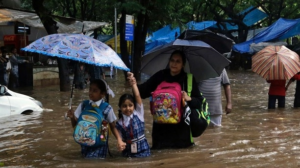 School children wade through a waterlogged street following heavy rains in Mumbai, India, Tuesday, Aug. 29, 2017. Heavy rains Tuesday brought Mumbai to a halt flooding vast areas of the city. (AP Photo/Rajanish Kakade)