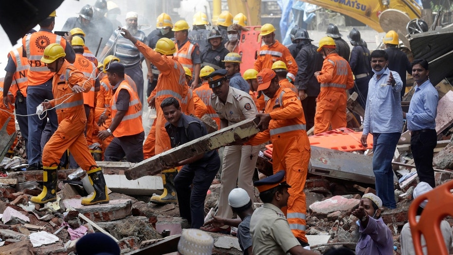 Rescue workers clear debris from the site of a building collapse in Mumbai, India, Aug. 31, 2017.