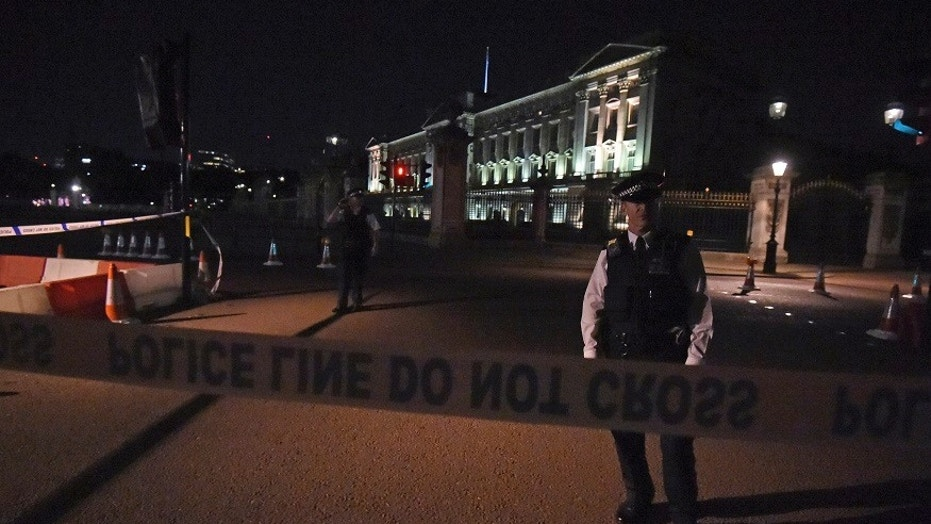 Police stand guard outside Buckingham Palace after an alleged attempted vehicle ramming incident.