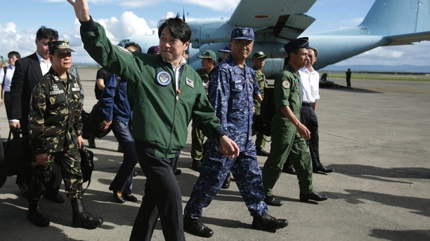 Japanese Defense Minister Itsunori Onodera, center, waves as he arrives at the airport in Tacloban, central Philippines on Sunday, Dec. 8, 2013. Onodera went to typhoon-ravaged Tacloban to look at the magnitude of the disaster for additional Japanese aid. (AP Photo/Aaron Favila)