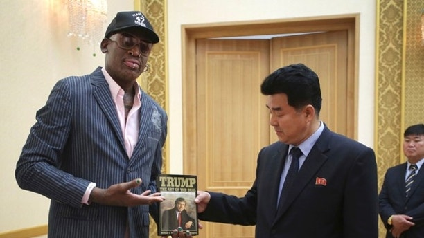 "In this June 15, 2017, file photo, former NBA basketball star Dennis Rodman presents a book titled ""Trump The Art of the Deal"" to North Korea's Sports Minister Kim Il Guk Thursday, June 15, 2017, in Pyongyang, North Korea. (AP Photo/Kim Kwang Hyon, File)"