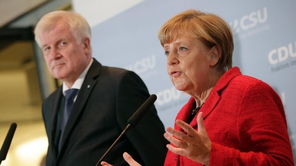 German Chancellor Angela Merkel, right, and the Governor of the German State of Bavaria, Horst Seehofer, left, address the media during a statement about  their talks on the migrant influx   prior to a meeting of lawmakers  at the German federal parliament, Bundestag, in Berlin, Germany, Tuesday, Nov. 3, 2015. (AP Photo/Michael Sohn)