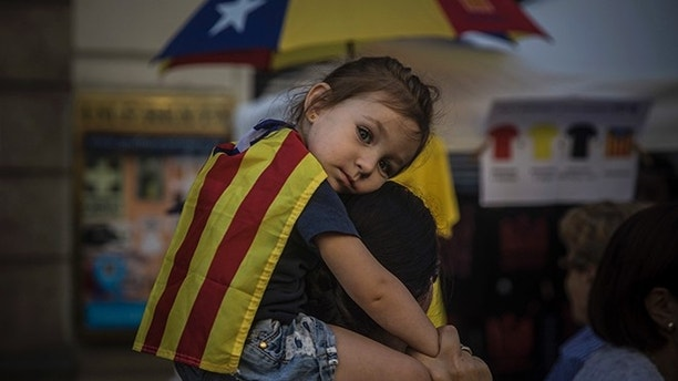 "EDS NOTE : SPANISH LAW REQUIRES THAT THE FACES OF MINORS ARE MASKED IN PUBLICATIONS WITHIN SPAIN A woman carries a girl on her shoulders wearing an ""estelada"" or independence flag, during the Catalan National Day in Barcelona, Spain, Monday, Sept. 11, 2017. Hundred of thousands of people are expected to demonstrate in Barcelona to call for the creation of a new Mediterranean nation, as they celebrate the Catalan National Day holiday. (AP Photo/Santi Palacios)"