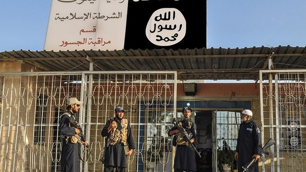 This undated image posted on a militant website on Friday, Sept. 19, 2014, file photo, which has been verified and is consistent with other AP reporting, shows Islamic State group policemen standing guard in front of a police station in Nineveh province, Iraq.