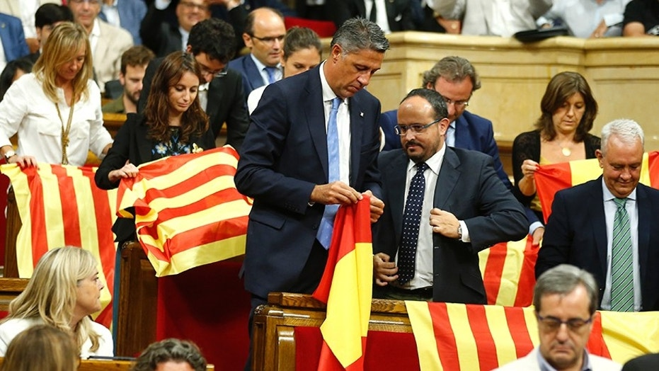 Members of the Catalan Popular Party display Spanish flags just before abandoning the session ahead of the voting, during a plenary session at the Parliament of Catalonia in Barcelona, Spain, Wednesday, Sept. 6, 2017. Catalan lawmakers are voting on a bill that will allow regional authorities to officially call an Oct. 1 referendum on a split from Spain, making concrete a years-long defiance of central authorities, who see the vote as illegal. (AP Photo/Manu Fernandez)