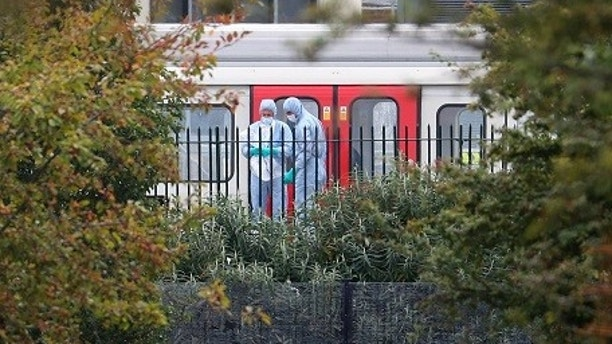 Forensic investigators search next to a London underground tube at Parsons Green station in London, Britain, September 15, 2017. REUTERS/Hannah McKay - RC18C6E3FD30