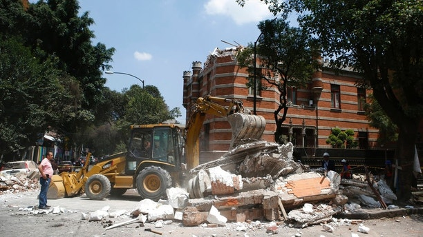 A bulldozer removes debris from a partially collapsed building after an earthquake in Mexico City, Tuesday, Sept. 19, 2017. A powerful earthquake jolted central Mexico on Tuesday, causing buildings to sway sickeningly in the capital on the anniversary of a 1985 quake that did major damage. (AP Photo/Rebecca Blackwell)