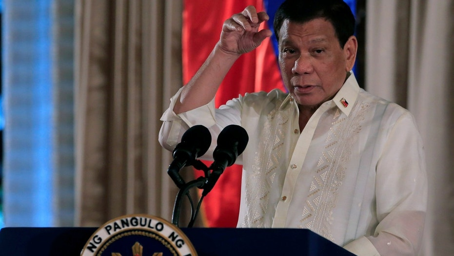 FILE: Philippine President Rodrigo Duterte gestures as he delivers his speech, during the oath taking of Philippine National Police