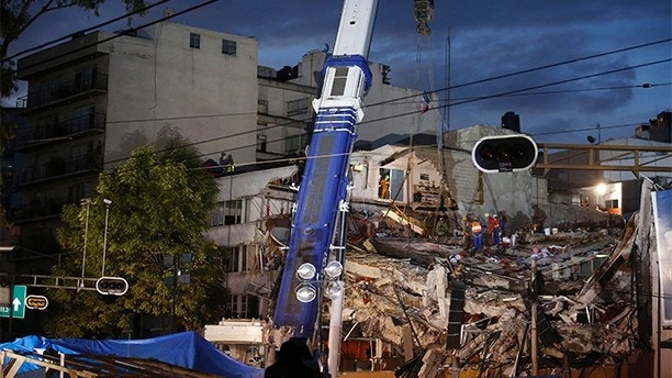 Israeli and Mexican rescue workers use a crane to lift a section of the building as rescue workers race against the clock to reach possible survivors trapped inside a office building in the Roma Norte neighborhood of Mexico City, in the early morning hours of Saturday, Sept. 23, 2017. A 7.1 magnitude earthquake Tuesday toppled more than three dozen buildings in the capital, leaving at least 46 people believed missing in this office building alone.(AP Photo/Rebecca Blackwell)