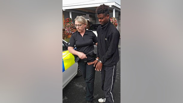 * SUN EXCLUSIVE HOLD FOR PRINT * Paul Edmunds from Caersws, Wales opened his car boot after arriving home from a break to France with friends, to find an illegal imigrant hiding inside. Pictured is the imigrant being led away by police officer after being discovered back in Wales.  Andy Kelvin /The Sun/News Syndication