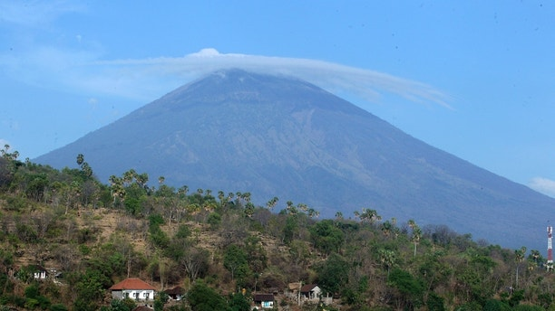 UPDATES CAPTION - Mount Agung volcano is seen in Amed, Bali, Indonesia, Tuesday, Sept. 26, 2017. More than 57,000 people have fled the surrounds of Mount Agung volcano on the Indonesian tourist island of Bali, fearing an imminent eruption, officials said Tuesday. (AP Photo/Firdia Lisnawati)