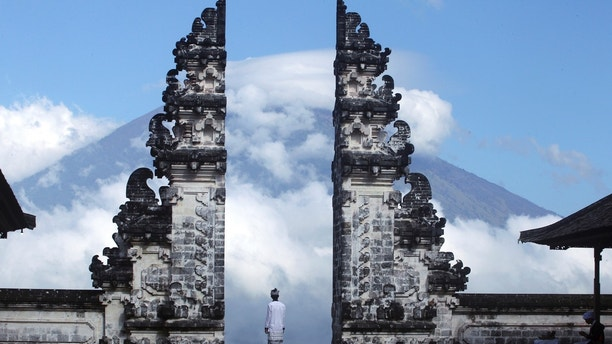 Balinese man watches Mount Agung volcano almost covered with clouds as he stands at a temple in Karangasem, Bali, Indonesia, Tuesday, Sept. 26, 2017. An increasing frequency of tremors from the volcano indicates magma is continuing to move toward the surface and an eruption is possible, a disaster agency official said Tuesday. Tourists are cutting short their stay to the island, where an eruption would force the airport to close and strand thousands. (AP Photo/Firdia Lisnawati)