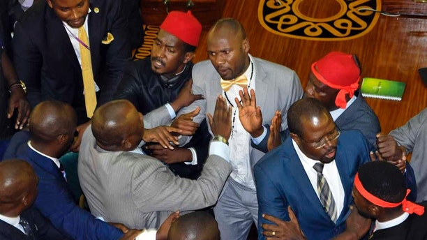 Ugandan lawmakers brawl in the Parliament in Kampala, Uganda Tuesday, Sept. 26, 2017. A fight broke out in Uganda's parliament Tuesday amid efforts to introduce legislation that could extend the president's decades-long hold on power. After opposition lawmakers accused some colleagues on the government side of carrying a gun, a brawl ensued in which lawmakers pushed and threw punches at each other. (AP Photo/Ronald Kabuubi)