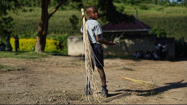 In this Wednesday, May 31, 2017 photo, a boy sweeps outside the assembly hall during break at the Side-By-Side Boetheo School in Rakai, Uganda. The school assists mostly orphans who were previously out of school but now receive scholarship aid from a donor if they satisfy criteria such as having a birth certificate. (AP Photo/Ben Curtis)
