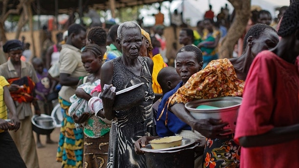 FILE - In this Tuesday, June 6, 2017 file photo, South Sudanese refugees queue to receive a lunch of maize mash and beans, at the Imvepi reception centre, where newly arrived refugees are processed before being allocated plots of land in nearby Bidi Bidi refugee settlement, in northern Uganda. The Trump administration on Wednesday, Sept. 6, 2017 imposed sanctions on two senior members of South Sudan's government, a former official, and three South Sudanese companies for undermining peace, security and stability in the crisis-stricken nation. (AP Photo/Ben Curtis, File)