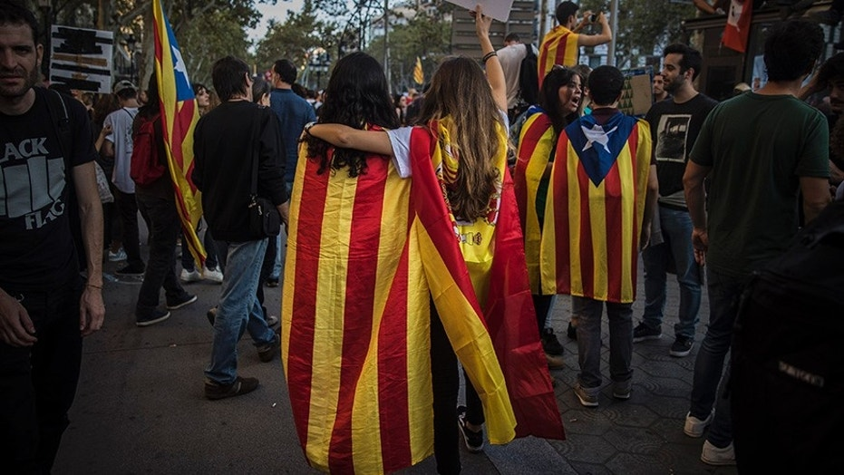 Two girls, one with a Catalan independence flag wrapped on her shoulders walks together with another one with a Spanish flag demonstrated in Barcelona in protest at what they say was police brutality during a referendum on Catalonia's secession from Spain.