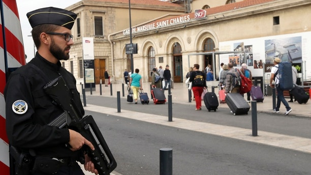 A police officer stands guard while passengers enter the Marseille Saint Charles train station, a day after a man fatally stabbed two women outside the train station, in Marseille, southern France, Monday, Oct. 2, 2017. The assailant was killed by soldiers immediately after the attack, the latest of several targeting France. (AP Photo/Claude Paris)