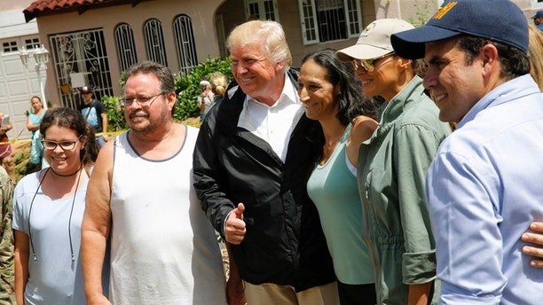 U.S. President Donald Trump and first lady Melania Trump pose with residents while surveying hurricane damage in San Juan, Puerto Rico, U.S., October 3, 2017. REUTERS/Jonathan Ernst - HP1EDA31E9U0O