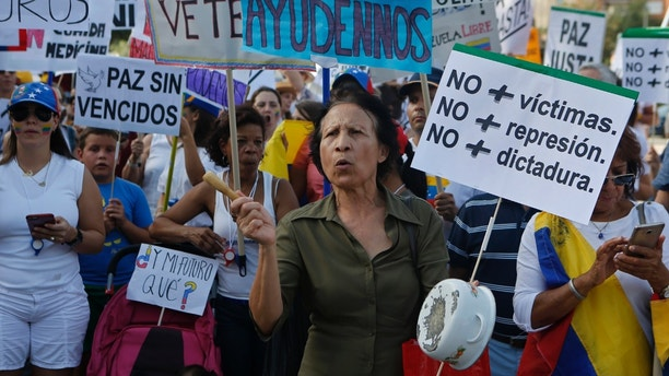 A woman bangs a cooking pot as Venezuelan residents shout slogans during a protest against the Venezuelan government in Madrid, Spain, Sunday, July 30, 2017. President Nicolas Maduro asked for global acceptance on Sunday as he cast an unusual pre-dawn vote for an all-powerful constitutional assembly that his opponents fear he'll use to replace Venezuelan democracy with a single-party authoritarian system. Main banners read 'Help us. No more victims, No more repression. No more dictatorship. My future? Peace without losers'. (AP Photo/Paul White)