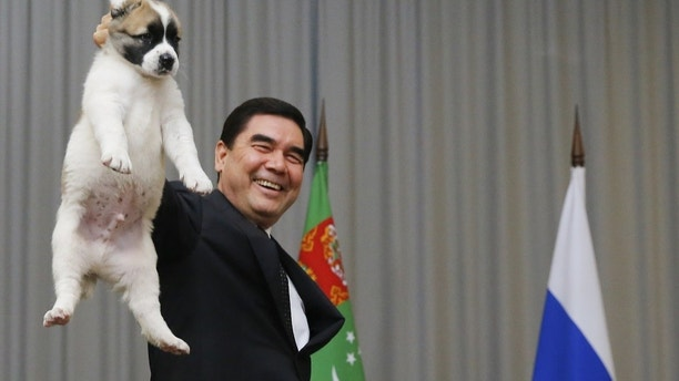 Turkmenistan's President Gurbanguly Berdimuhamedov (L) demonstrates a Turkmen shepherd dog, locally known as Alabai, before presenting it to his Russian counterpart Vladimir Putin during a meeting in Sochi, Russia October 11, 2017. REUTERS/Maxim Shemetov - UP1EDAB0PUM56