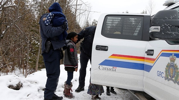 The children of a woman who told police that she and her family were from Sudan are placed in a vehicle as they are all taken into custody by Royal Canadian Mounted Police (RCMP) officers after arriving by taxi and walking across the U.S.-Canada border into Hemmingford, Quebec, Canada February 12, 2017. Picture taken February 12, 2017. REUTERS/Christinne Muschi - RC1AEB01C480